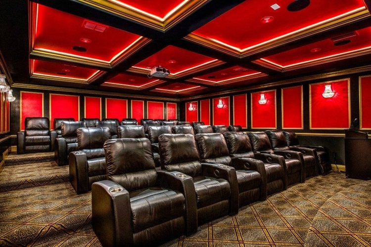 In-house movie theater with leather cinema-style seating and projector screen