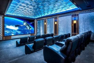 This home theater has a projector screen and tiered seating