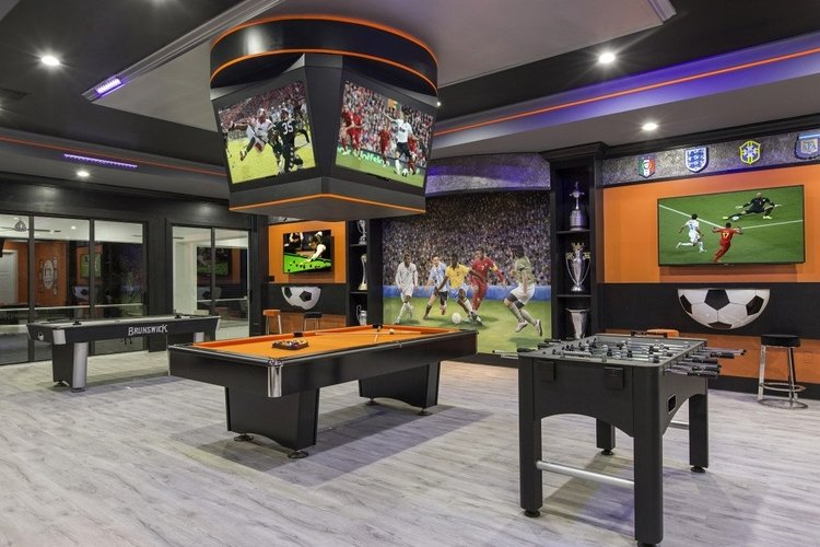 Sports themed game room with multiple TV screens