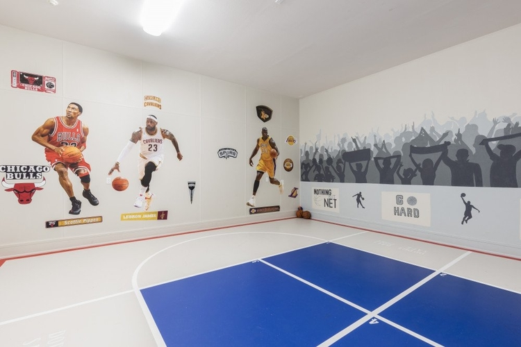 Indoor basketball court with wall vinyls of players and crowd