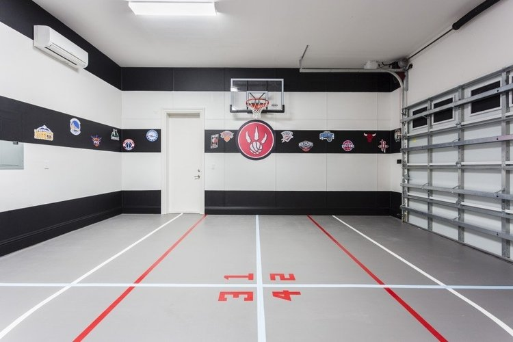 Indoor basketball court with NBA team logos on the wall