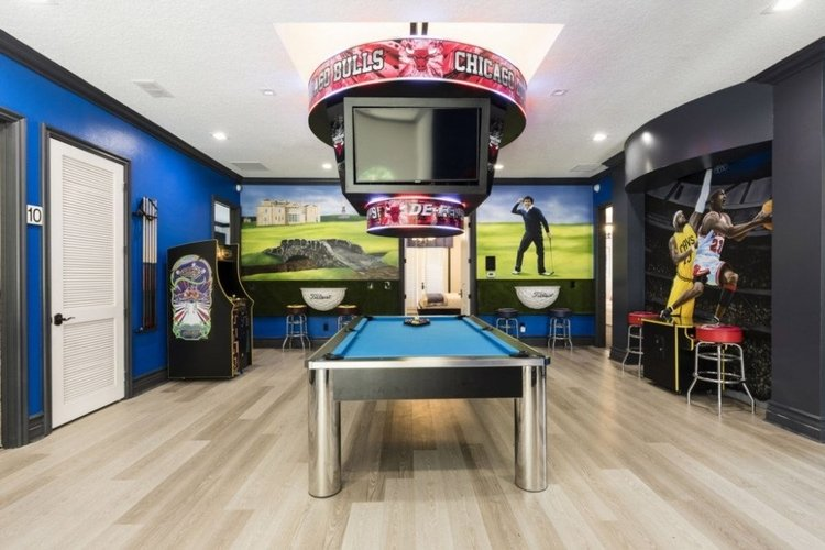Sport themed game room with pool table, multiple TV screens and arcade games