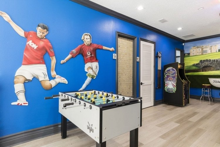 Game room with foosball table and Manchester United footballers painted on the wall