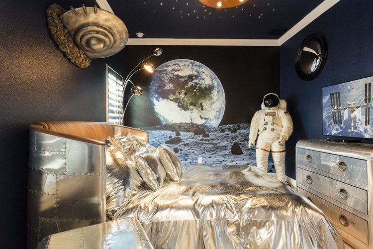Space themed bedroom with silver bedding and life-size astronaut