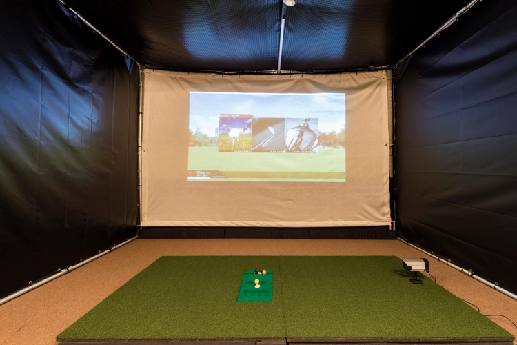 This home features an indoor golf simulator with projector screen