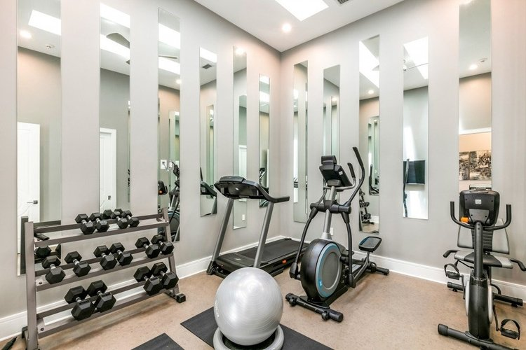 A modern mirrored gym with weights and state of the art equipment