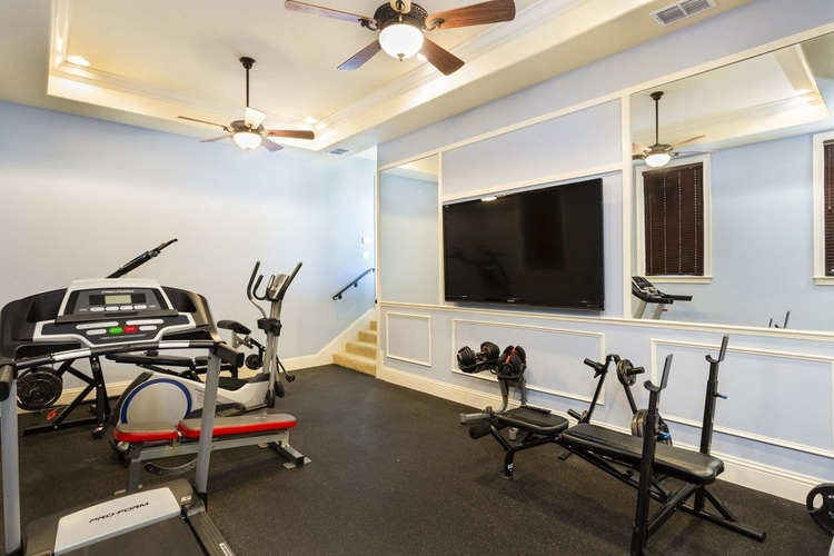 This private gym features a large flat-screen TV on the wall
