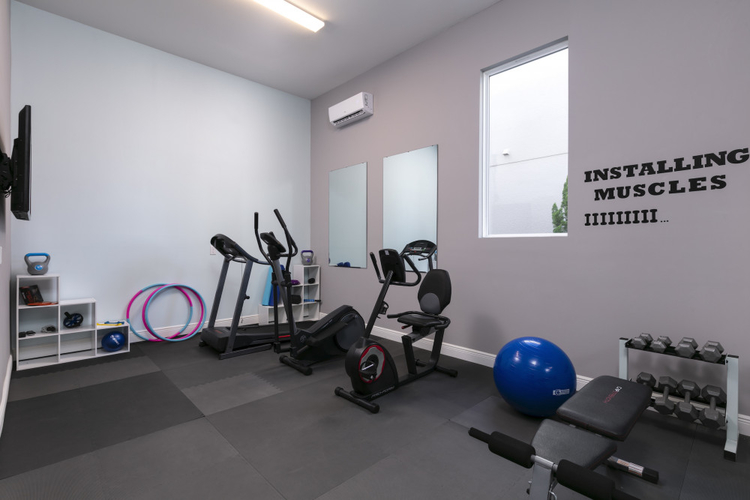 The villa features a gym with a tv and a range of equipment