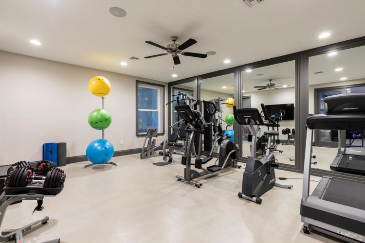 The villa features a modern gym with a range of equipment