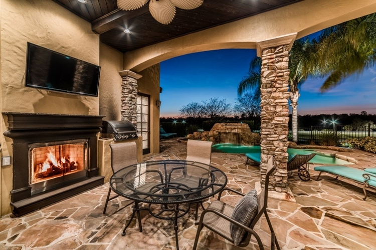 Outside the covered lanai features a flat-screen TV and fireplace