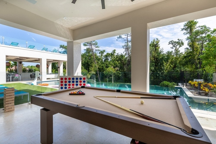 The covered lanai features outdoor games and a billiards table