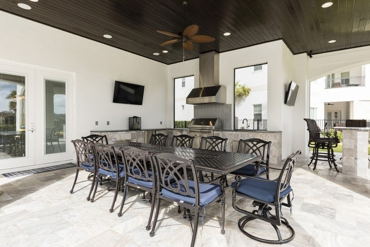 There is a covered lanai with an alfresco dining area and an outdoor kitchen