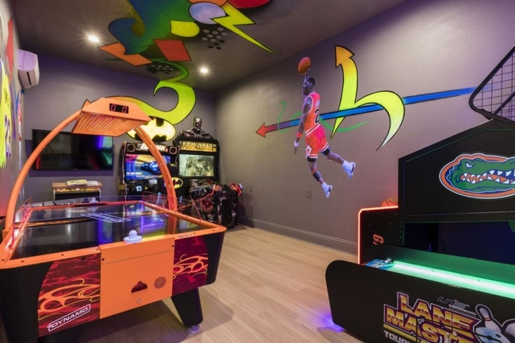 This game room features an air hockey table and a bowling simulator