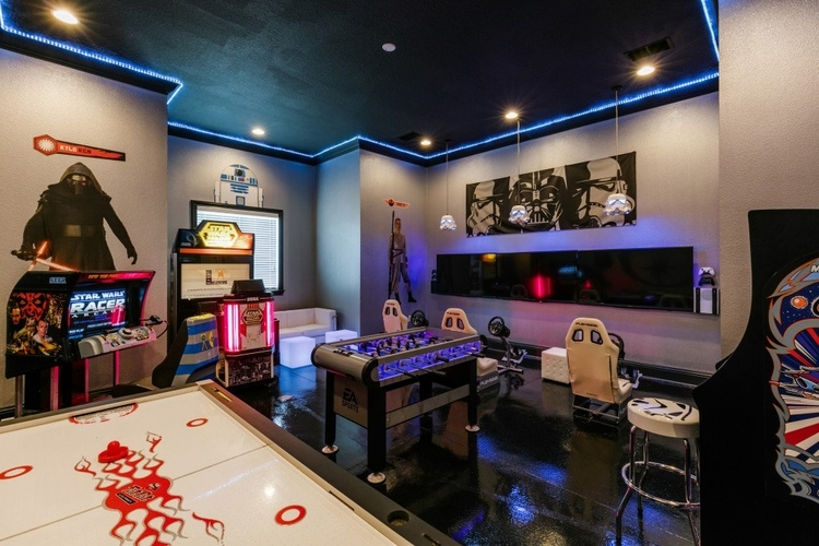 This game room features arcade video games and flat-screen TVs with games consoles