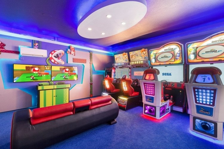 The game room features a relaxing leather couch and 2 flat-screen TVs for gaming