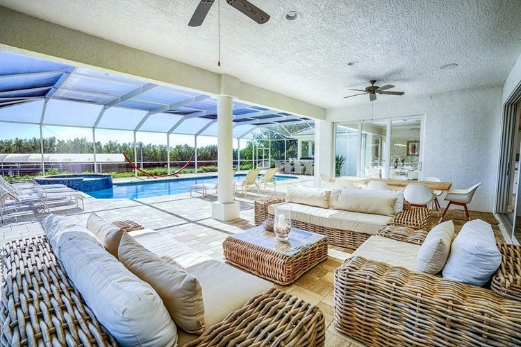 Outside, there is a huge covered lanai with outdoor seating and an alfresco dining area
