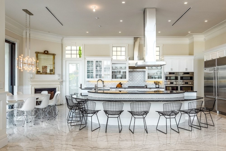 Inside the villa, there is a modern fully-equipped kitchen with a large breakfast bar with seating