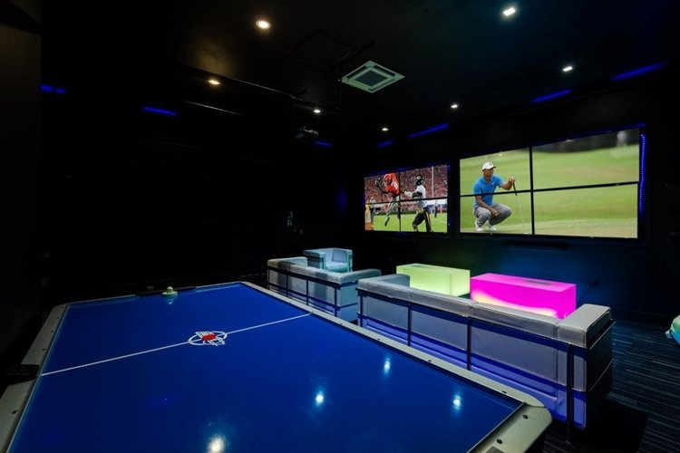 There is a game room downstairs with an air hockey table, lounge seating and a video wall