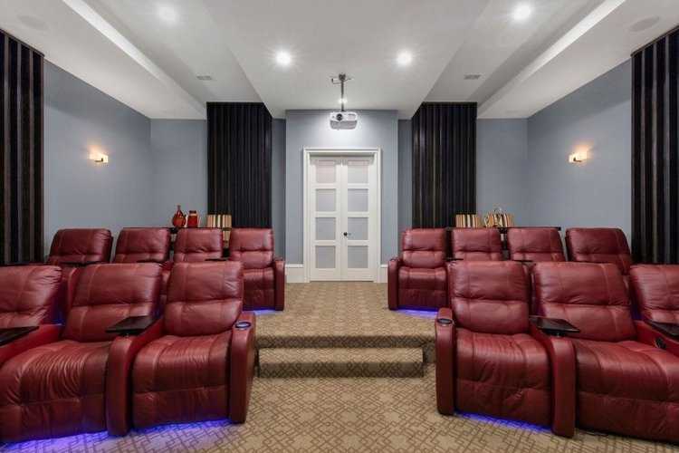 The villa has a home theater with tiered cinema-style seating and a projector screen