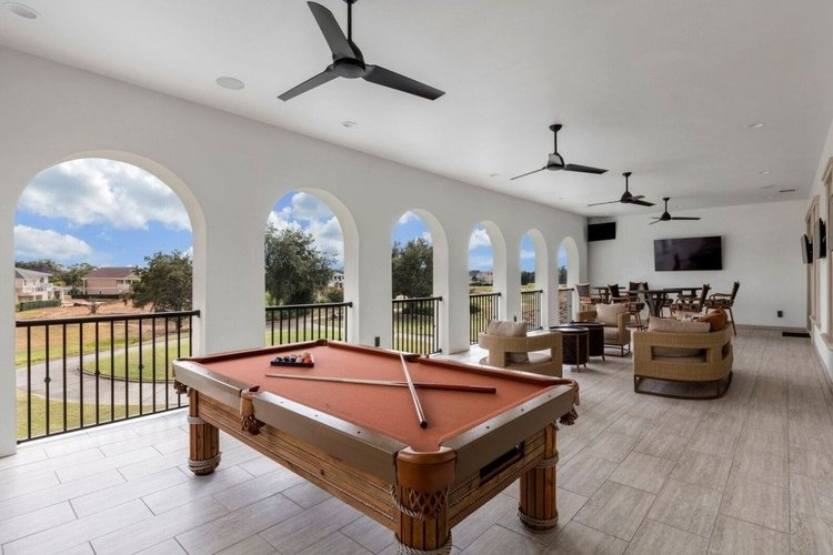 This villa has a first-floor balcony overlooking the resort, with lounge seating and a pool table
