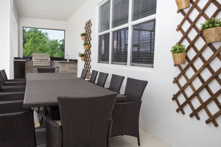 Under the covered lanai there is an alfresco dining area and an outdoor kitchen