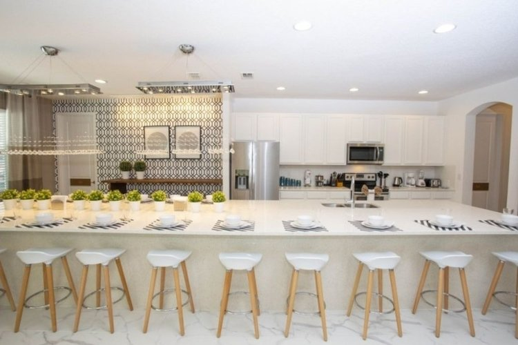 There is a modern fully equipped kitchen with a breakfast bar and bar stool seating