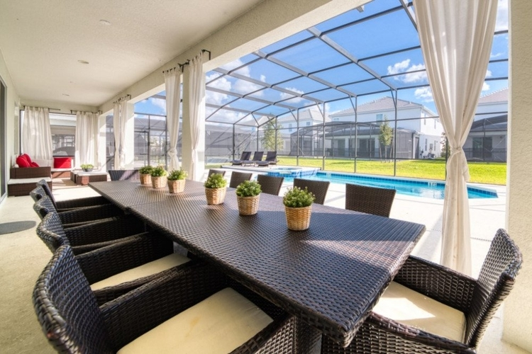 The covered lanai outside has lounge seating and an alfresco dining area