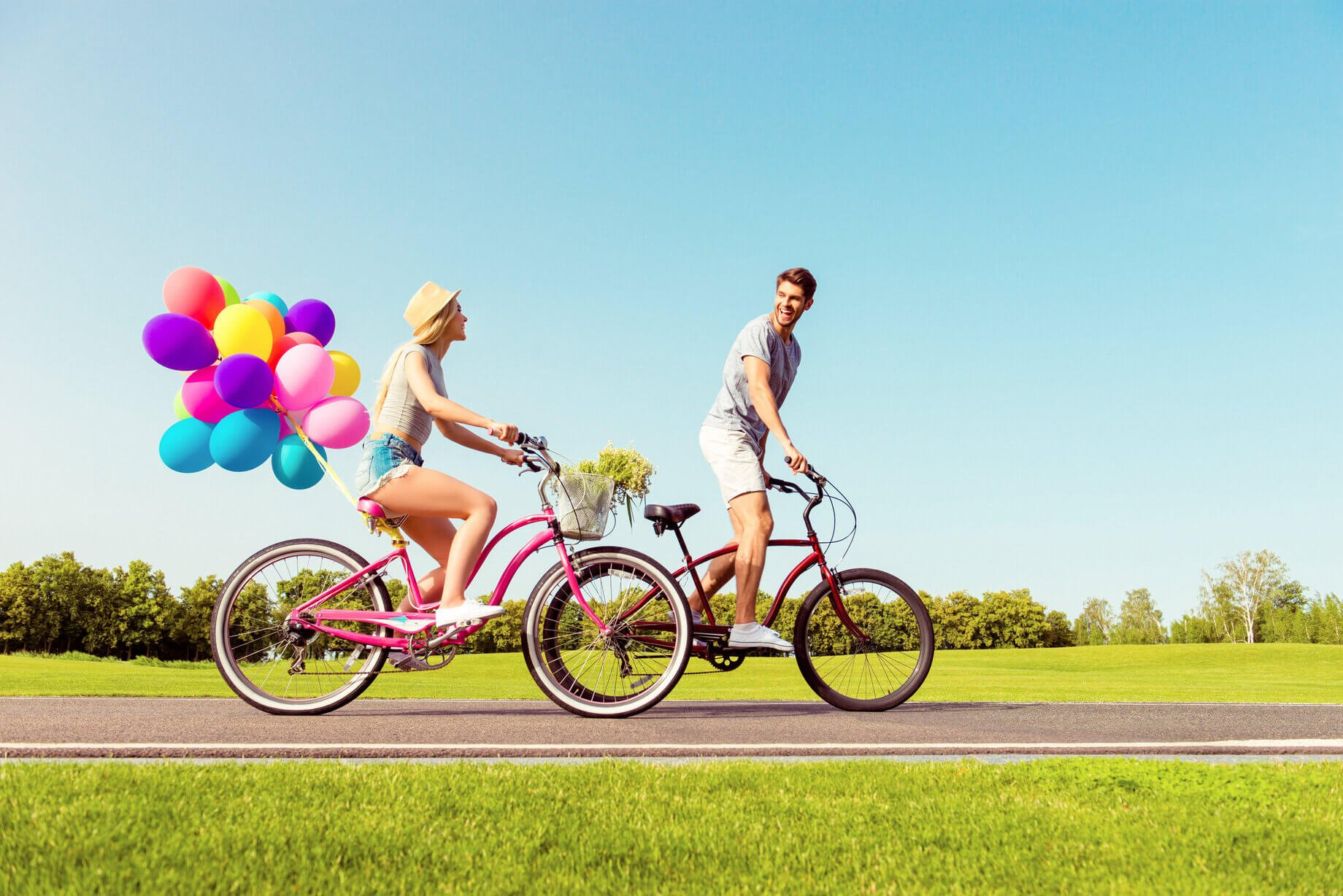 Couple on bikes with colourful balloons