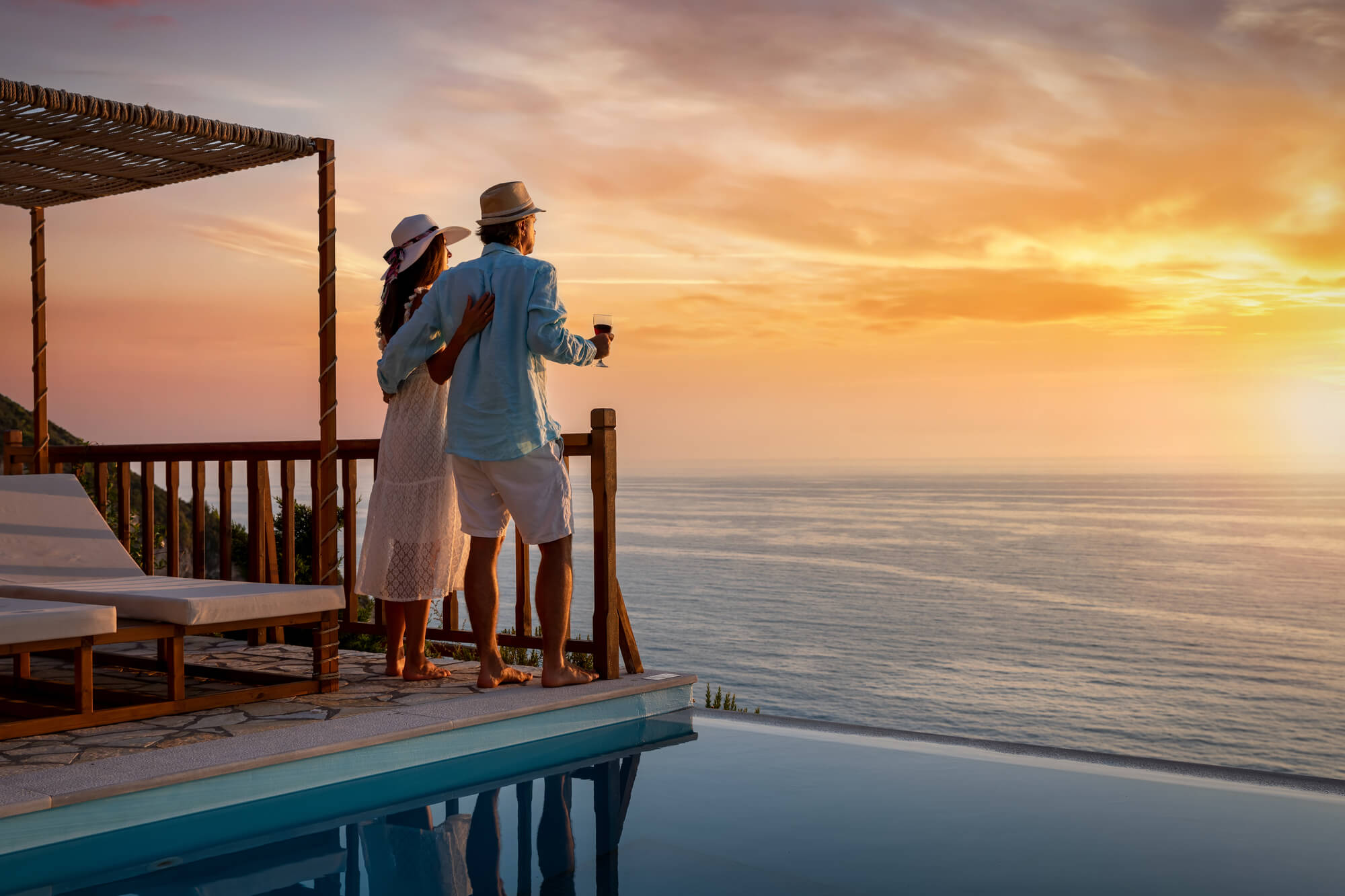A couple standing on a balcony at sunset looking at the ocean