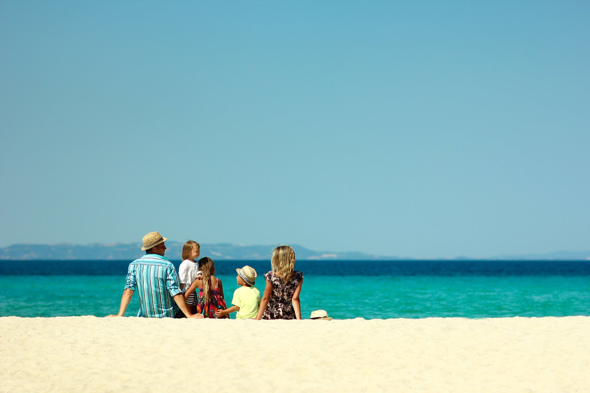 A family of 2 adults and 3 children sitting on a white sandy beach looking out to sea