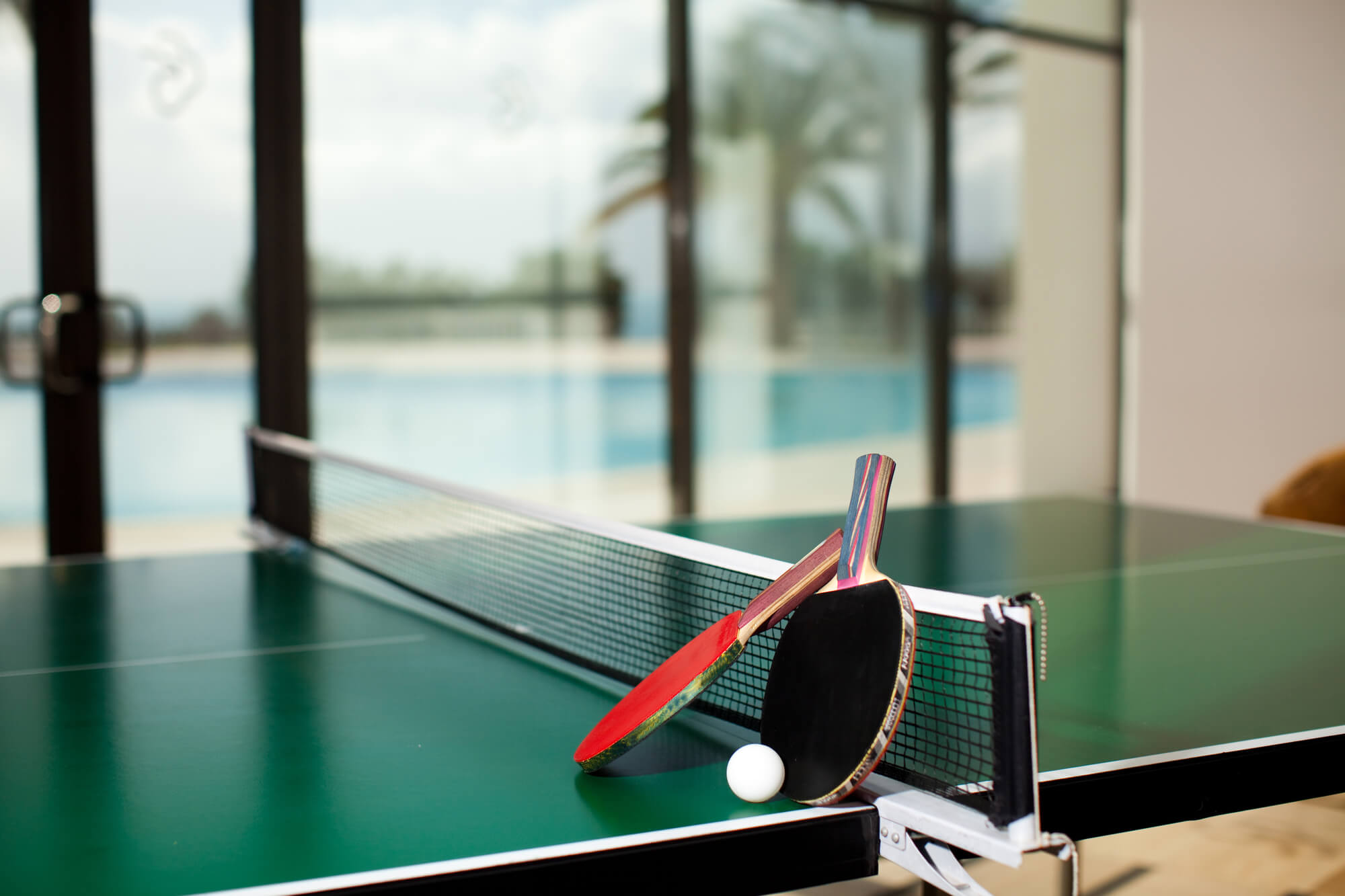 A ping pong table in a room with a swimming pool and palm trees outside