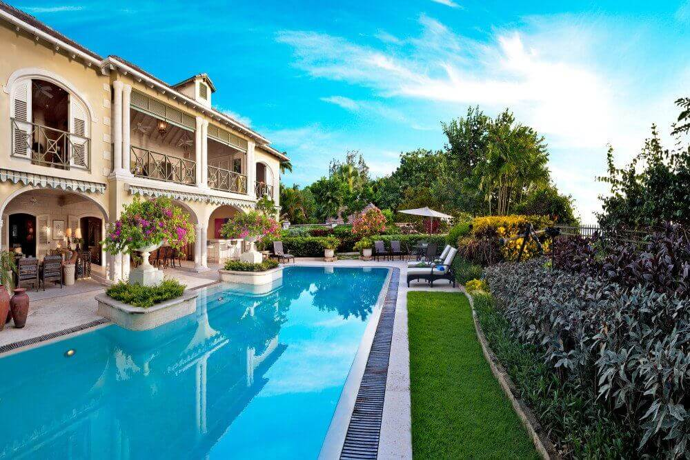 A grand two-story Barbados villa with flowering plants outside, a large pool, an outside patio area and landscaped gardens.