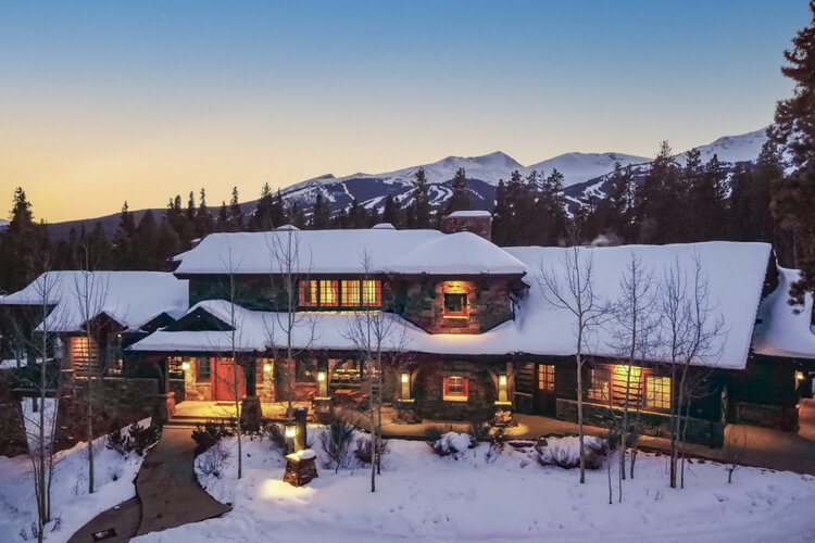 A large house in the mountains covered in snow