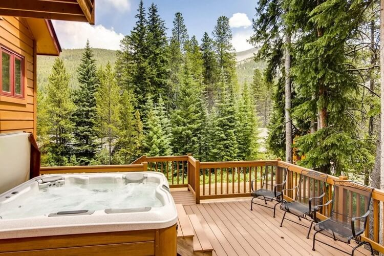 A wooden cabin the forest with a jacuzzi and decked area