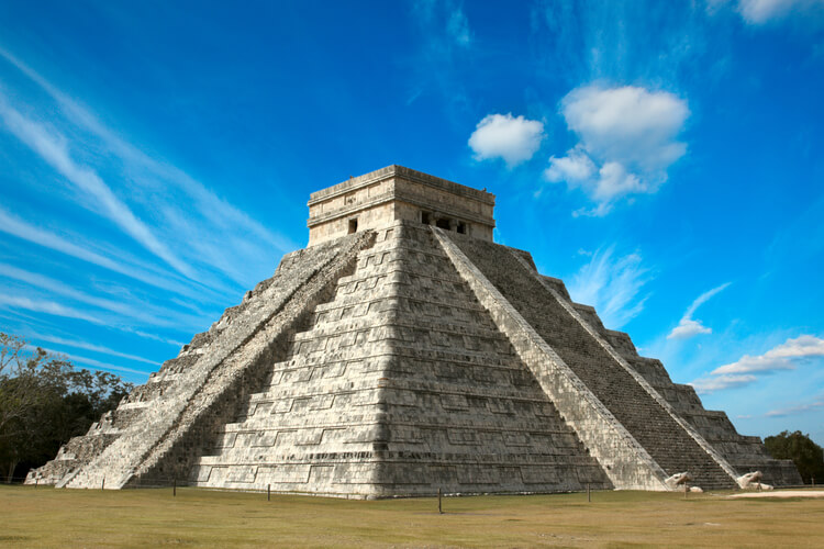The pyramid of Chichen Itza in front of a blue sky.