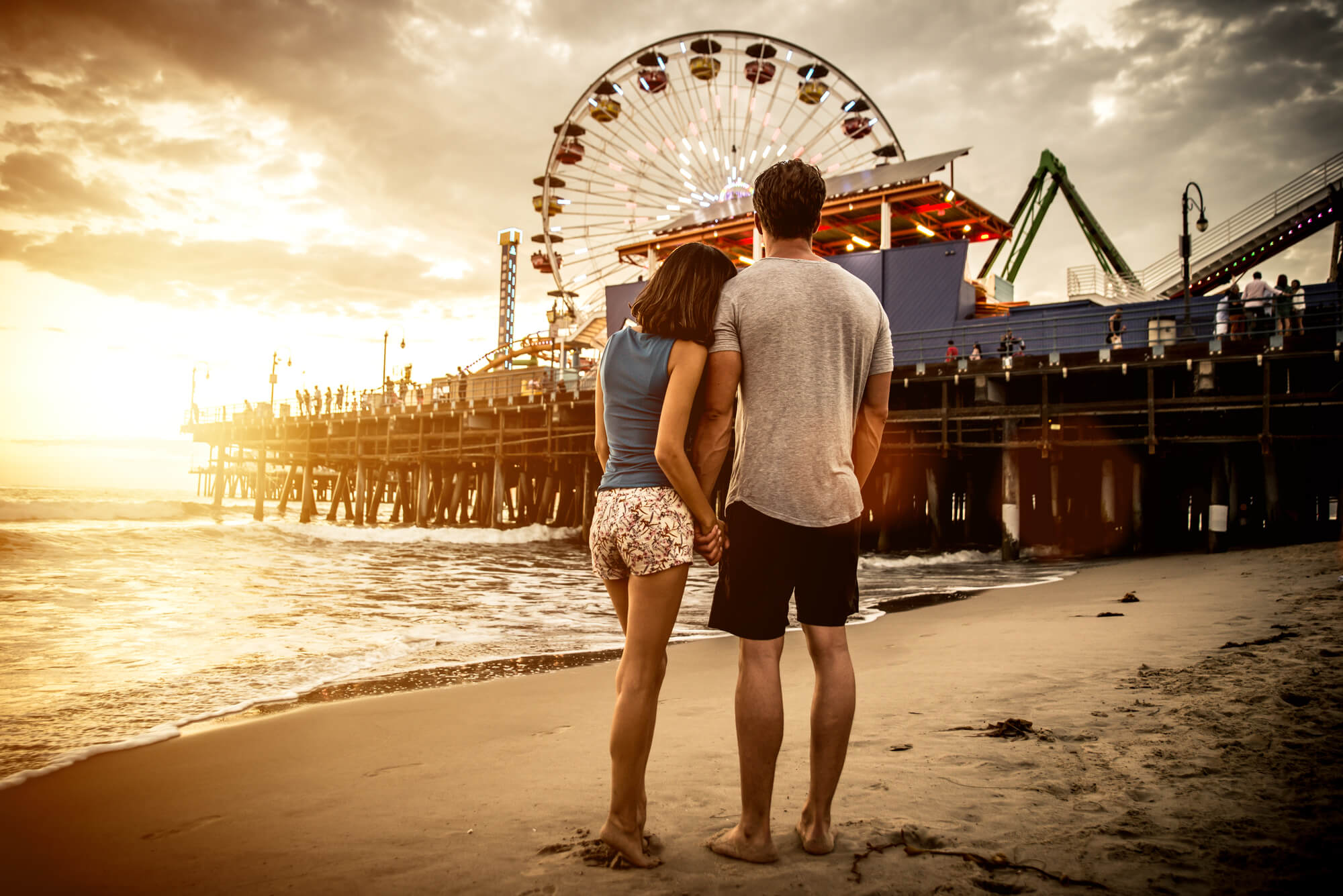 A couple on a California beach at sunset