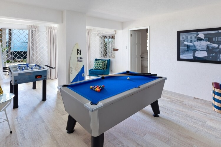 A room containing a pool table, a foosball table and a surfboard