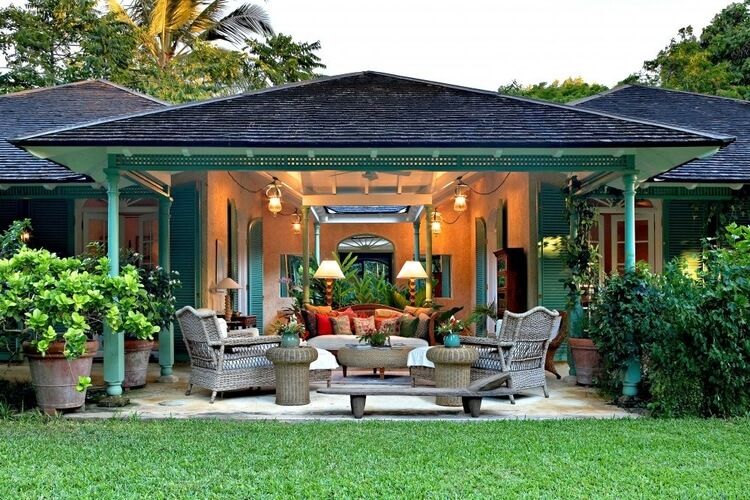 An open-air seating area in a large Barbados villa, surrounded by plants and a manicured grass lawn