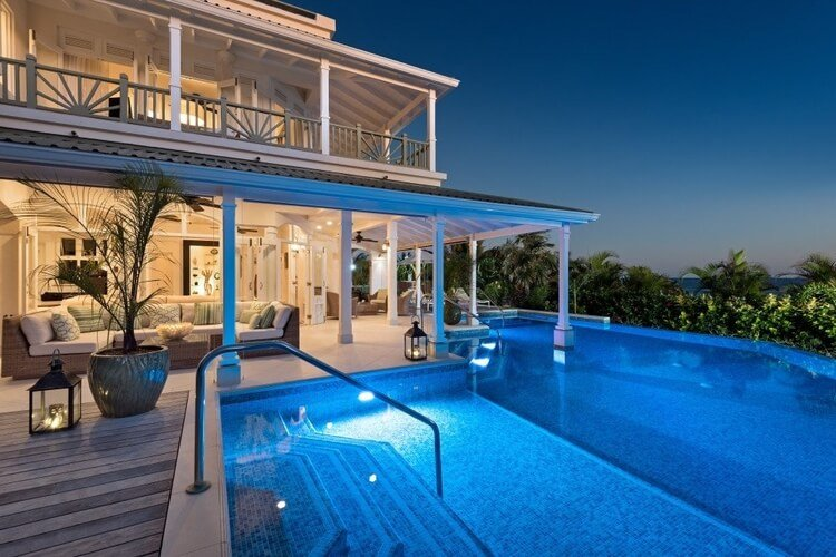 A two-story villa in Barbados with a large infinity pool, overlooking palm trees.