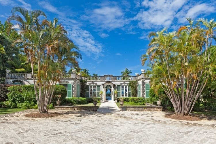The front door of a large villa in Barbados, with tall palm trees on either side