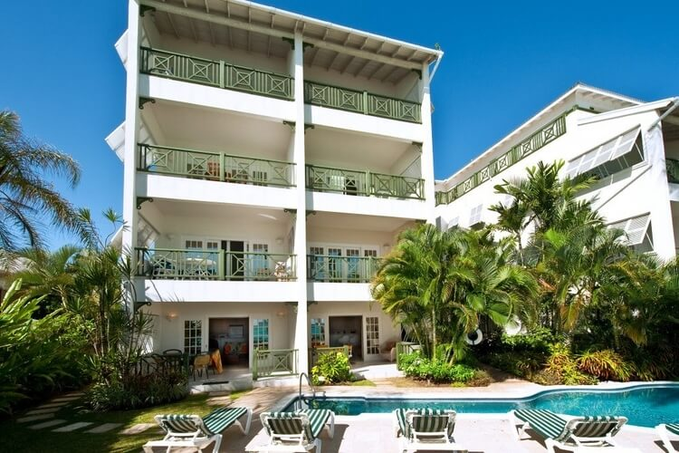 An apartment block in Barbados with green balconies, overlooking a swimming pool and palm trees.