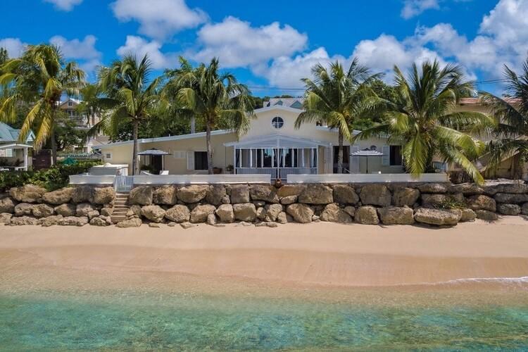 A yellow beachfront villa in Barbados, overlooking a white sandy beach a the Caribbean Sea.
