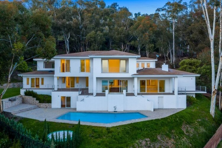 A large white Malibu villa with a private pool, surrounded by trees