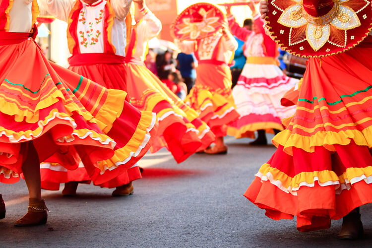 Mexican ladies in traditional red and yellow dresses dancing in the street