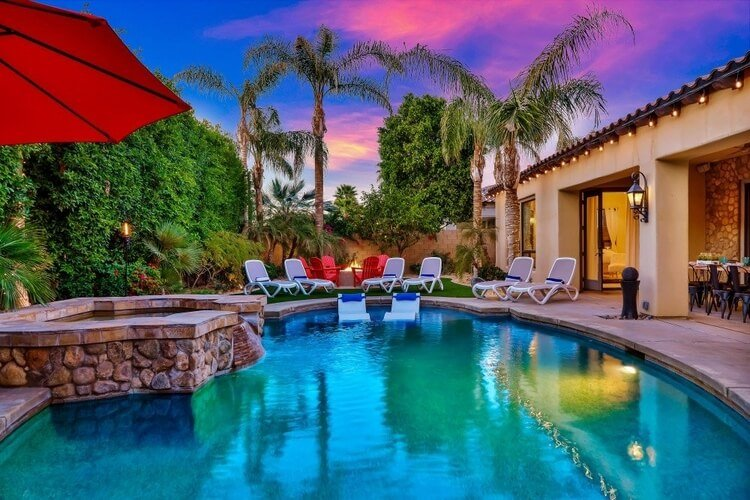 A beautiful Palm Springs villa with a large private pool, outdoor seating and palm trees