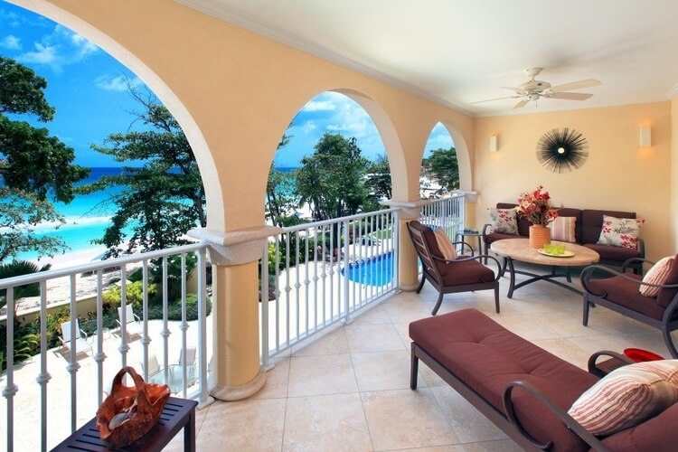 A Barbados family villa with a covered seating area overlooking trees, a beach and the sea