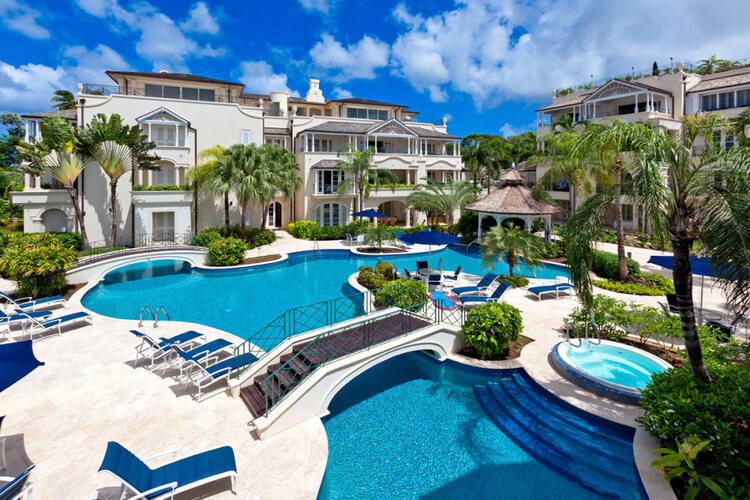 A resort in Barbados with a large swimming pool in the center, surrounded by apartments.