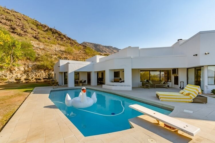 A white modern villa with a private pool with a large inflatable swan in it