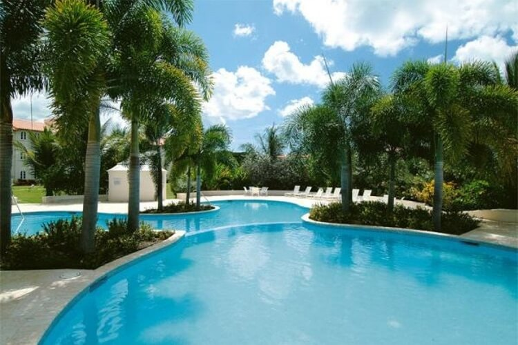 Sugar Hill Tennis Village resort pool, surrounded by palm trees.
