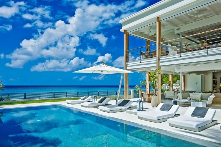 A two-story villa in Barbados with an outdoor pool and sun bathing chairs, overlooking the Caribbean Sea.